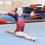 Young gymnast doing the splits during a competition